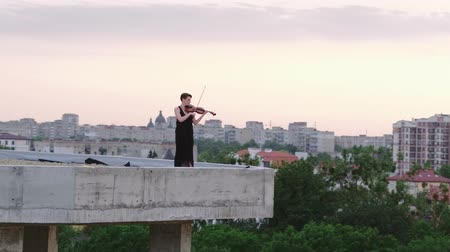 seçkinler : Woman In Evening Dress Playing The Violin On. Beautiful Young Woman On The Roof Of The Building. Aerial View. Stok Video
