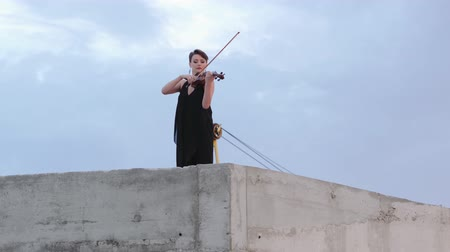 バイオリニスト : Woman In Evening Dress Playing The Violin On. Beautiful Young Woman On The Roof Of The Building. Aerial View. 動画素材