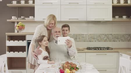 veselí : Happy Family Uses A Tablet For Video Communication. Family Toasting At Dinner Table At Home In Kitchen
