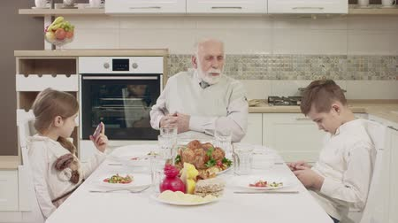 внучка : Grandpa Communicates With Grandchildren At The Table Before A Family Dinner. Family Toasting At Dinner Table At Home In Kitchen