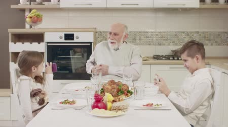veselí : Grandpa Communicates With Grandchildren At The Table Before A Family Dinner. Family Toasting At Dinner Table At Home In Kitchen
