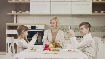 veselí : Mom Communicates With Her Children At The Table During A Family Dinner. Family Toasting At Dinner Table At Home In Kitchen Dostupné videozáznamy