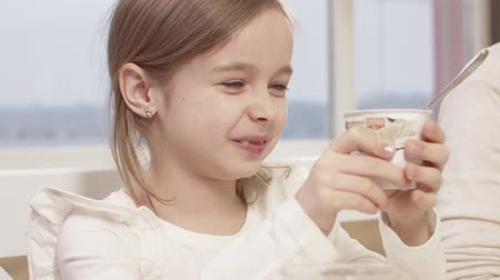 veselí : Little Girl Eats A Delicious Chocolate Mousse During A Family Dinner. Family Toasting At Dinner Table At Home In Kitchen