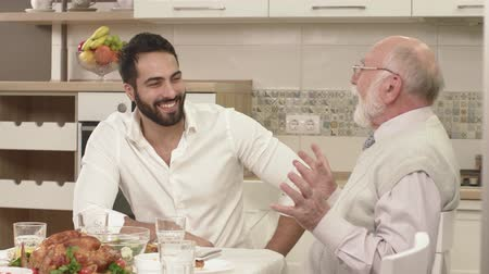 veselí : Friendly Conversation Between Two Men During A Family Dinner. Family Toasting At Dinner Table At Home In Kitchen