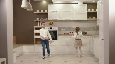 jóvenes discoteca : Brother And Sister Have Fun And Dance In The Kitchen. Archivo de Video