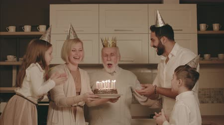 üfleme : Family Celebrating The Grandfathers Birthday. Elderly Man Blows Out Candles On The Cake.