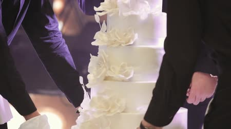 casar : Waiters Carry A Wedding Cake In Hall. Close-up View Of A Bride And Groom Cutting Their Wedding Cake.