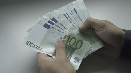euro banknotes : Businessmans hands counting hundred Euro bills at a table