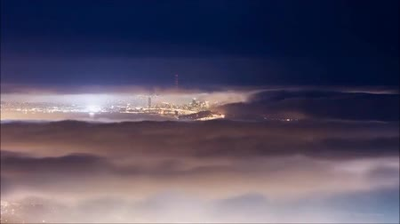 Flying over the deep night timelapse clouds with moon light. Seamlessly looped animation. Flight through moving cloudscape over night city lights. Perfect for cinema, background, digital composition.