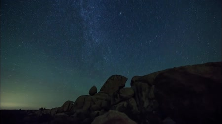large stones of various forms are under the starry night sky. view of the starry sky. Often flying shooting stars. Night starry sky rotates above the ground.