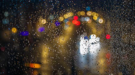 světlomety : Night cars lights through rainy window.