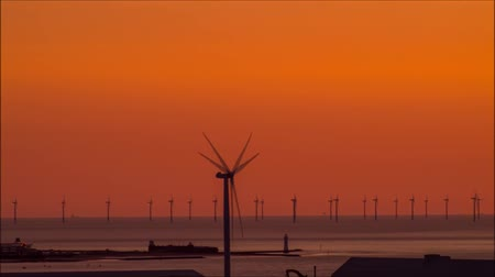 Air Windmills in The Water Off The Coast of Liverpool. the Sun Went Down Over the Horizon Sky Orange.