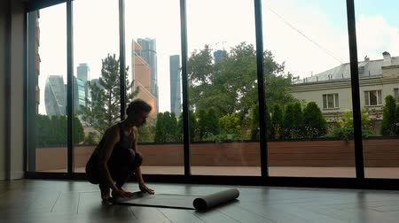 sakk : A young woman unfolds a mat in a yoga room next to a large window overlooking the skyscrapers.yoga room