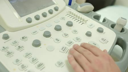 sonography : The doctors hand close-up. How does the ultrasound machine work. Doctor works on the ultrasound machine clicks on the buttons.