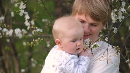 цветущий : Mom with a short haircut, with a baby in her arms, looking at a flowering tree