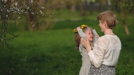 çelenk : Happy mother and daughter in the park in spring playing with dandelions