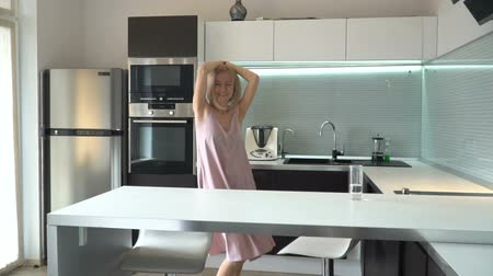 Cheerful middle-aged woman dancing in the kitchen Wideo