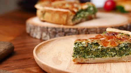 flan : Quiche a savoury open tart or flan consisting of pastry crust with spinach mushrooms cheese. Stock Footage