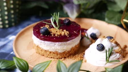 blueberry cheesecake : Delicious homemade cheesecake with berry sauce set on wooden plate.