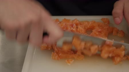 omega : chef hand with knife cutting salmon fillet on a board. Stock Footage