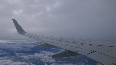 летчик : View from airplane with wing flying in the sky between layers of clouds.