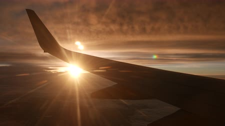 wschód słońca : View of airplane with silhouette wing flying in the sky over sunset cloud with the beautiful golden sun.