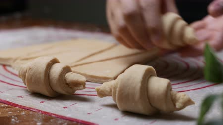 tereyağlı : pastry chef hand making croissant on wooden board.