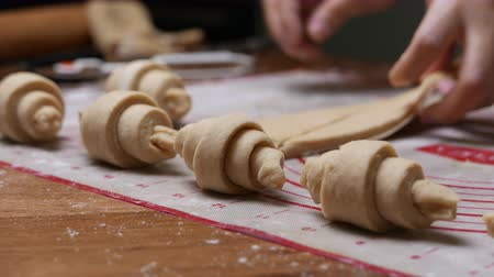 colesterol : pastry chef hand making croissant on wooden board.