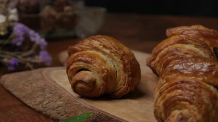 podnos : Fresh croissant a flaky, viennoiserie pastry on wooden board.