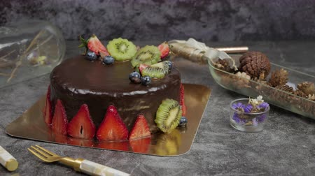 blueberry cheesecake : sweet pastry dessert chocolate cake with strawberry, kiwi and blueberry set on kitchen table.