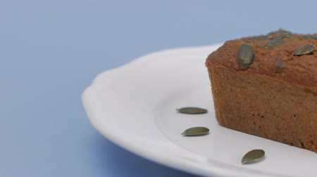 baked pumpkin : Gluten-Free pumpkin bread with pumpkin seed in white plate set on light blue background.