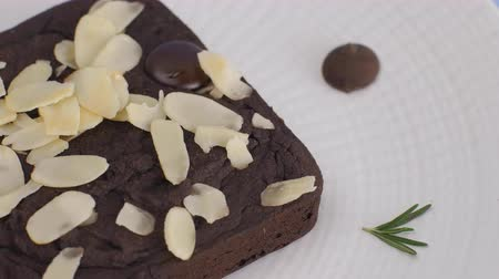 geçiştirmek : Chocolate Brownie with almond slice in white plate set on light blue background. Stok Video