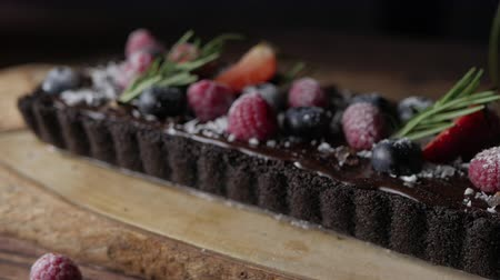 Rectangular Tart Chocolate cheesecake with fresh berries. delicious dessert for celebrate. Set on wooden table background.