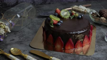 чизкейк : sweet pastry dessert chocolate cake with strawberry, kiwi and blueberry set on kitchen table.