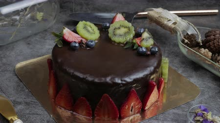 sweet pastry dessert chocolate cake with strawberry, kiwi and blueberry set on kitchen table.