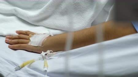 Hospital patient hand with saline solution in Intravenous Drip Dropper in hospital.