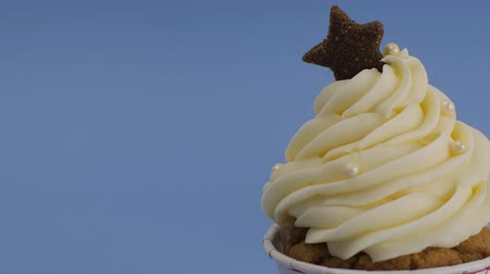Cupcake muffin with whipping cream for celebrate Christmas. set on light blue background. Stock mozgókép