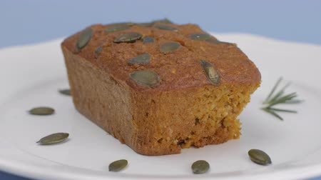 Gluten-Free pumpkin bread with pumpkin seed in white plate set on light blue background.
