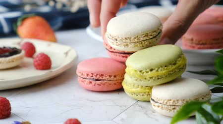 macarons : Slow-motion hand pick Colorful French macarons cakes desert set on party table. Stock Footage