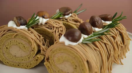 Chestnut roll cake with fresh cream on brown background. Stock mozgókép