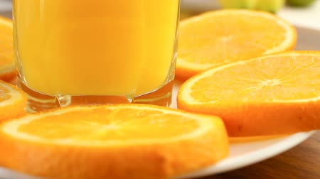 healthyfood : Fresh citrus fruits. Rotate Video footage of the concept of a healthy food and diet. Orange juice in a glass, with a background of different fruits: banana, lime, lemon, orange. Its spinning