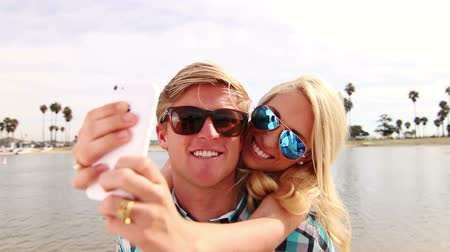 alma : Young Happy Couple Taking Selfie At Beach Stok Video