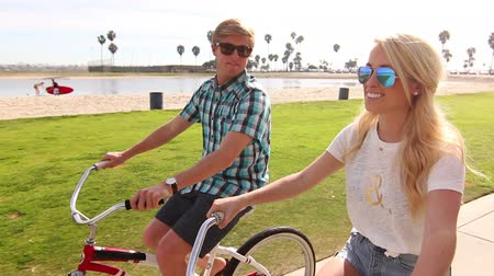 lifestyle : Young Happy Couple Riding Bikes At Beach