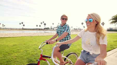 estilo de vida : Young Happy Couple Riding Bikes At Beach Slow Motion, Summer Lifestyle HD Vídeos