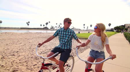 pěšina : Young Happy Couple Riding Bikes At Beach Slow Motion, Summer Lifestyle HD Dostupné videozáznamy