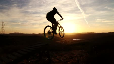 obstacles : Slow Motion Silhouette Of Man Mountain Biking Off Extreme Jump