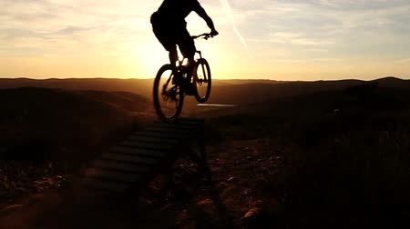 bisiklete binme : Silhouette Of Man Mountain Biking Off Extreme Jump Stok Video