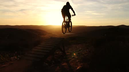 bisiklete binme : Slow Motion Silhouette Of Man Mountain Biking Off Extreme Jump