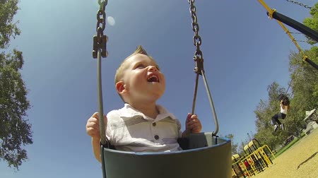 plac zabaw : Young Cute Baby Boy In Swing At Park  Wideo