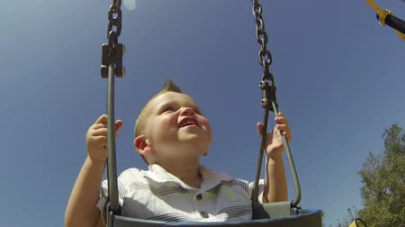 közepes : POV Cute baby boy in swing at park on summer day  Stock mozgókép